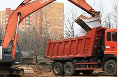 Гусеничный экскаватор погружает в красный самосвал строительные отходы