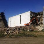 Оранжевый экскаватор-разрушитель сносит белое здание