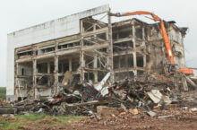 Процесс разрушения четырехэтажного здания специализированной техникой