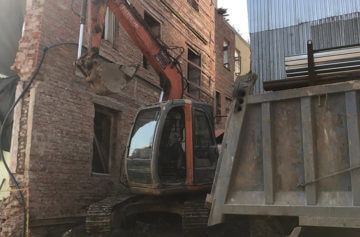 Снос ветхого трехэтажного здания при помощи специализированной техники