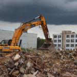 Работа экскаватора по уборке строительных отходов после сноса здания