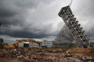Экскаватор работает с большим количеством строительного мусора