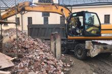 Рабочий управляет экскаватором, загружая строительный мусор в самосвал