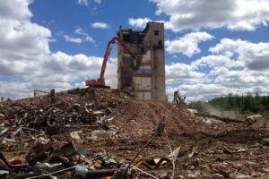 Экскаватор-разрушитель сносит ветхое здание