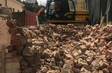 Процесс работы экскаватора и самосвала по погрузке и вывозу строительных отходов