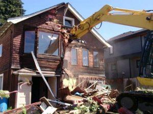 Экскаватор сносит старый дом