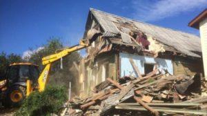 Снос старого деревянного здания экскаватором